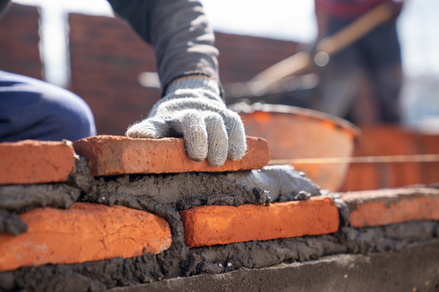 bricklayer-industrial-worker-installing-brick-masonry-with-trowel-putty-knife-construction-site 33835-1135